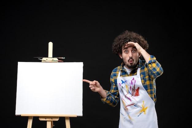 Vue de face jeune peintre masculin avec chevalet pour dessiner à la recherche sur un tableau noir