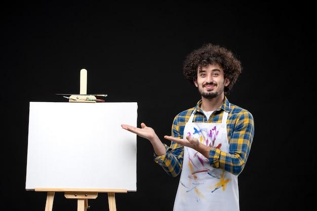 Vue de face jeune peintre masculin avec chevalet pour dessiner sur un tableau noir