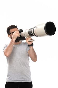 Une vue de face jeune photographe masculin en t-shirt gris et jeans noirs prenant des pousses sur le blanc