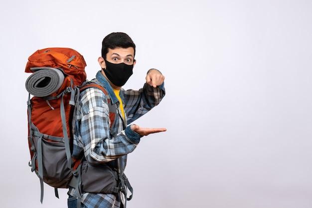 Vue de face jeune randonneur avec sac à dos et masque noir debout sur fond blanc