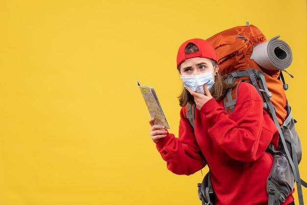 Vue de face jeune randonneuse avec sac à dos et masque tenant la carte mettant la main sur son menton