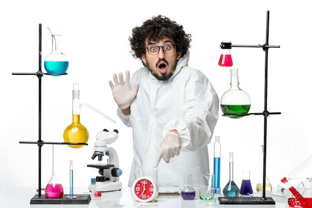 Vue de face jeune scientifique masculin en costume spécial blanc posant avec une expression surprise