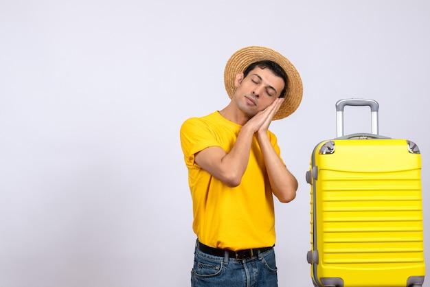 Vue de face jeune touriste debout près de valise jaune dormir