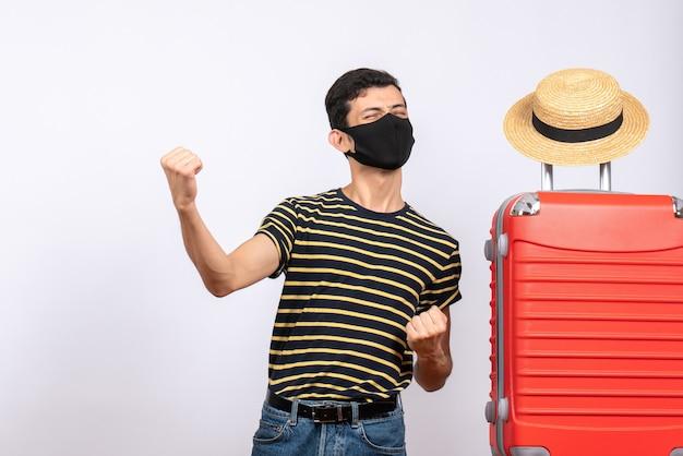 Vue de face jeune touriste exalté avec masque noir debout près de valise rouge montrant ses coups de poing