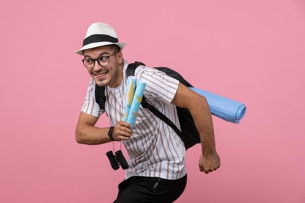 Vue de face jeune touriste masculin tenant des cartes sur fond rose clair