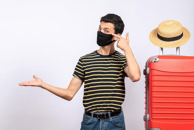 Vue de face jeune touriste avec masque noir debout près de valise rouge montrant quelque chose