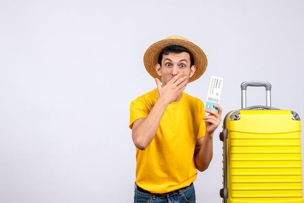 Vue de face jeune touriste perplexe debout près de valise jaune tenant un billet