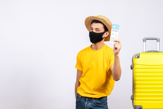 Vue de face jeune touriste en t-shirt jaune debout près de valise jaune tenant un billet de voyage