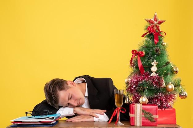 Vue de face jeune travailleur masculin assis avec des cadeaux de noël et arbre dormant
