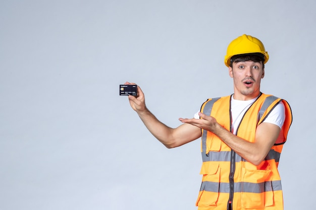 Vue de face jeune travailleur masculin avec carte bancaire noire sur fond blanc