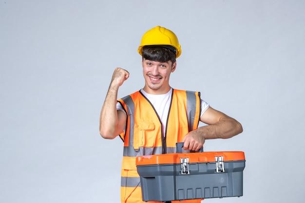 Vue de face jeune travailleur masculin avec valise à outils sur fond blanc