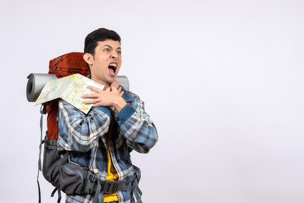 Vue de face jeune voyageur en colère avec sac à dos tenant la carte
