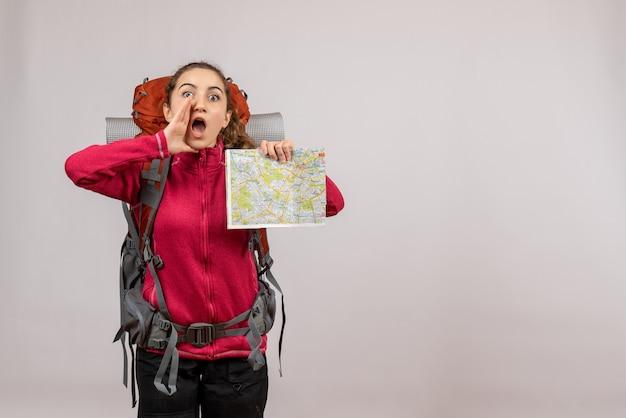 Vue de face jeune voyageur avec un grand sac à dos tenant une carte appelant quelqu'un copie place