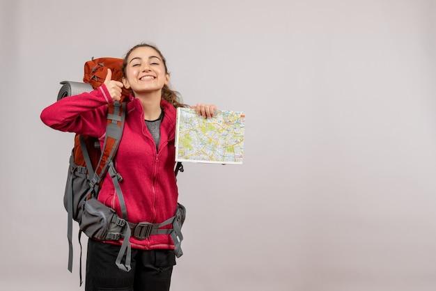 Vue de face jeune voyageur avec gros sac à dos pointant sur la carte donnant le pouce vers le haut