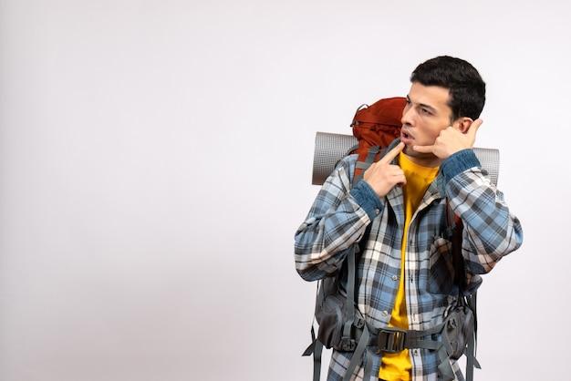 Vue de face jeune voyageur avec sac à dos faisant appelez-moi téléphone geste
