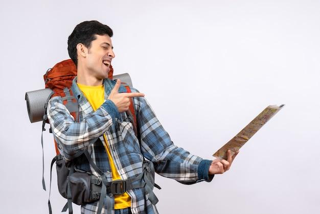 Vue de face jeune voyageur avec sac à dos pointant à l'endroit sur la carte