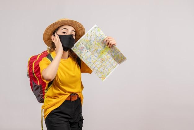 Vue de face jeune voyageur avec sac à dos rouge brandissant la carte