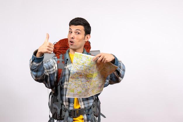 Vue de face jeune voyageur avec sac à dos tenant la carte abandonnant le pouce vers le haut