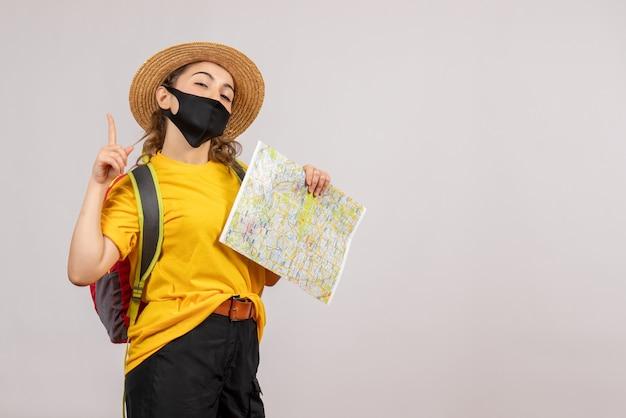 Vue de face jeune voyageur avec sac à dos tenant la carte pointant vers le haut