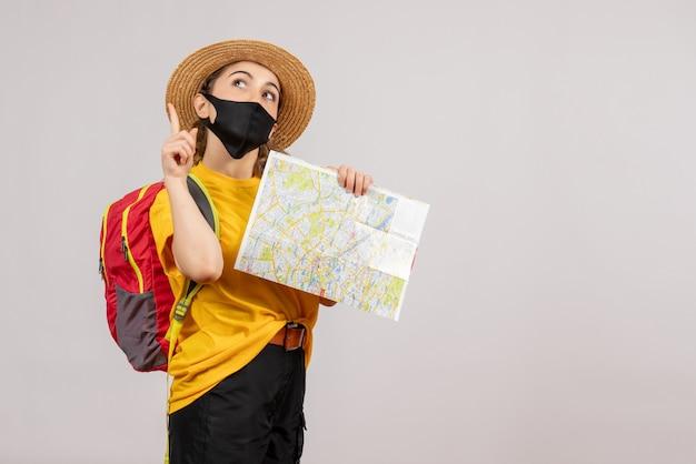 Vue De Face Jeune Voyageur Avec Sac à Dos Tenant La Carte Pointant Vers Le Haut Photo gratuit