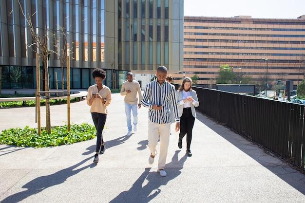 Vue de face de jeunes citoyens marchant dans la rue avec des téléphones