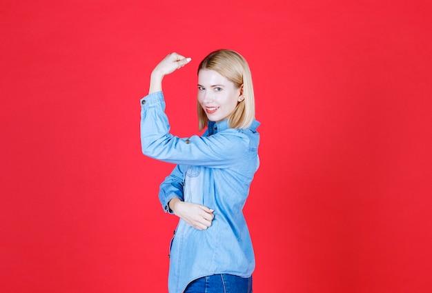 Vue de face des jeunes femmes lève le bras pour montrer le muscle