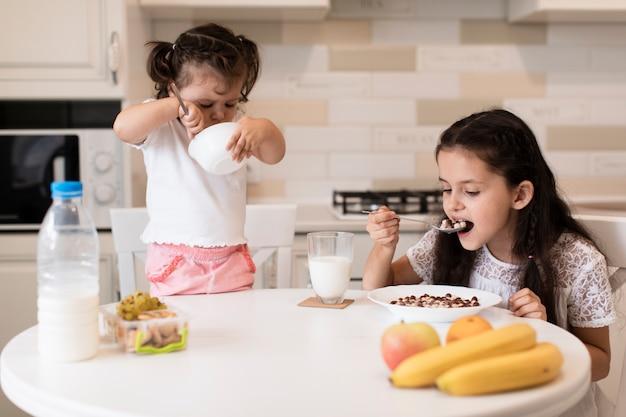 Vue de face des jeunes filles prenant son petit déjeuner