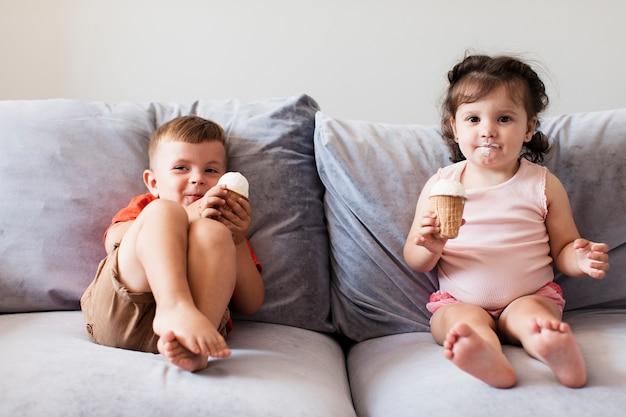 Vue de face des jeunes frères et sœurs sur le canapé