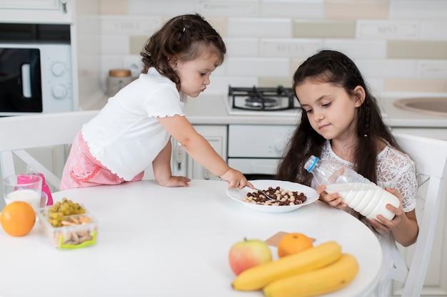 Vue de face des jeunes frères et sœurs prenant son petit déjeuner