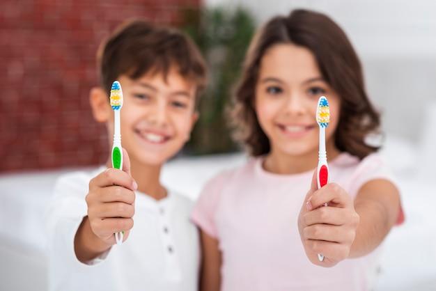 Vue de face des jeunes frères et sœurs tenant une brosse à dents