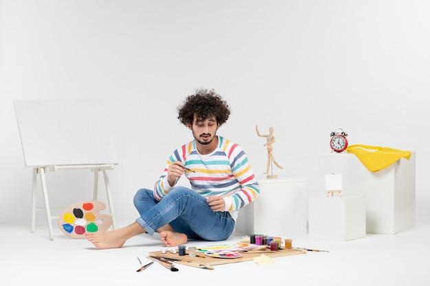 Vue de face de jeunes hommes dessinant des images avec des peintures sur un mur blanc