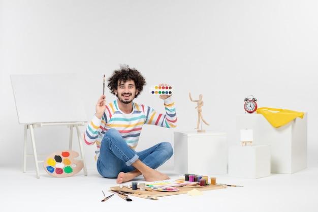 Vue De Face De Jeunes Hommes Dessinant Des Images Avec Des Peintures Sur Un Mur Blanc Photo gratuit