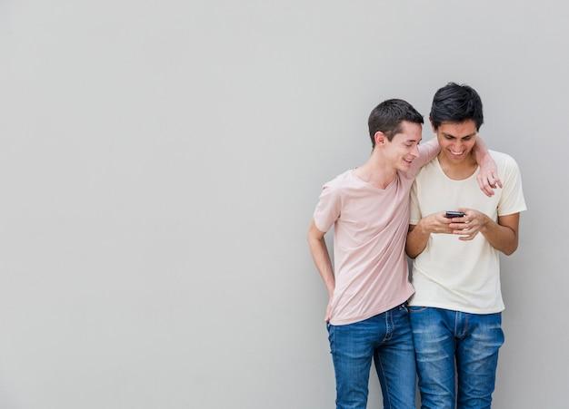Vue de face de jeunes hommes vérifiant un téléphone