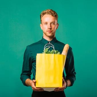 Vue de face joli homme tenant un sac d'épicerie