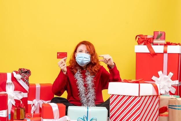 Vue de face jolie femme assise autour de cadeaux en masque avec carte bancaire sur jaune