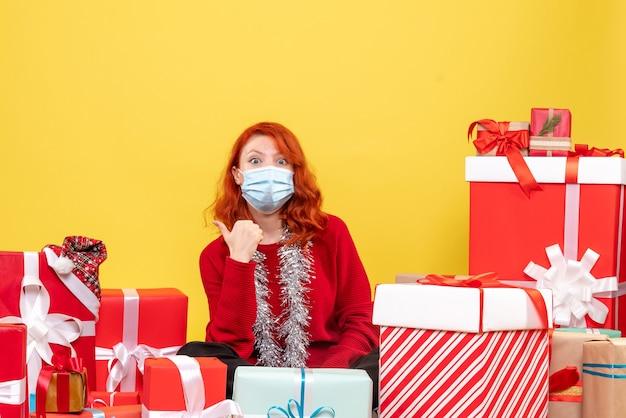 Vue de face jolie femme assise autour de cadeaux en masque sur jaune