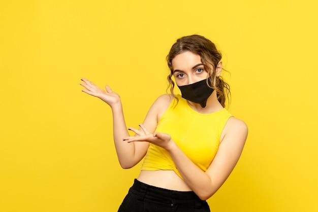 Vue de face de la jolie femme au masque noir sur jaune