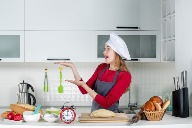 Vue de face jolie femme blonde en chapeau de cuisinier et tablier debout derrière la table de la cuisine