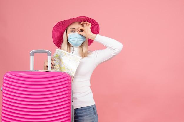 Vue de face jolie femme blonde debout près de la valise faisant des jumelles à main