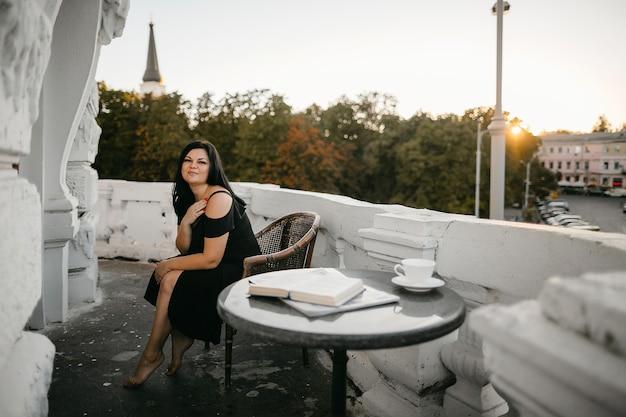 Vue de face d'une jolie femme brune en robe noire assise près d'une table basse avec vue sur la ville le soir ensoleillé.