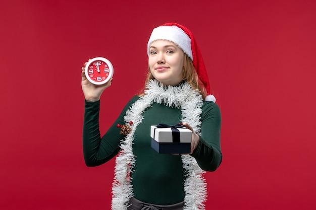 Vue de face jolie femme avec des cadeaux avec horloge sur fond rouge