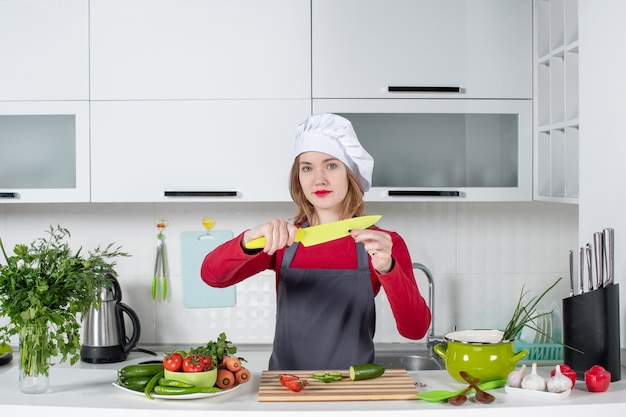 Vue de face jolie femme cuisinier en tablier brandissant un couteau