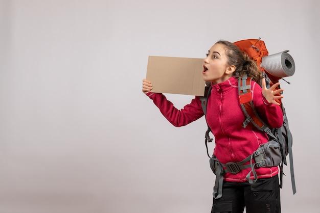 Vue de face d'une jolie femme étonnée avec grand sac à dos tenant du carton