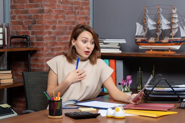 Vue de face d'une jolie femme étonnée vérifiant des documents au bureau