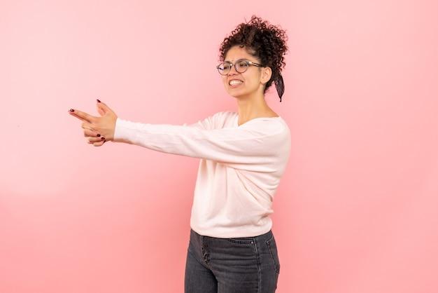 Vue de face de la jolie femme imitant le pistolet pose sur rose