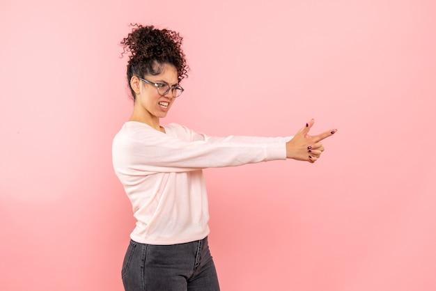 Vue de face de la jolie femme imitant le pistolet tenant sur rose