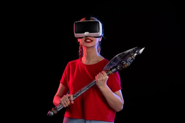 Vue de face d'une jolie femme jouant au vr avec une hache de combat sombre