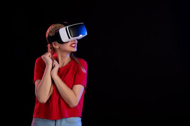 Vue de face d'une jolie femme jouant avec enthousiasme à la réalité virtuelle sur des jeux fantastiques à ultrasons sombres