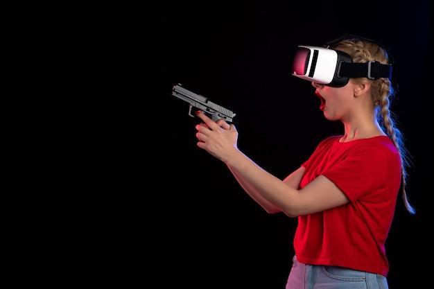 Vue de face d'une jolie femme jouant à la réalité virtuelle avec une arme à feu sur des guerriers sombres vikings samouraï