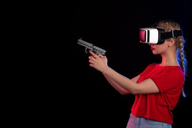 Vue de face d'une jolie femme jouant à la réalité virtuelle avec une arme à feu sur un jeu visuel de technologie d'agent sombre
